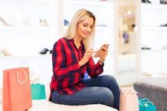 La jeune femme utilise un smartphone dans le magasin de mode Photos libres de droits