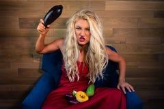 La jeune femme végétarienne s'assied sur le fauteuil sur le fond du mur en bois photographie stock libre de droits