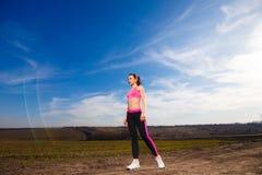 La jeune femme va chercher des sports sur le fond de ciel bleu Photo stock