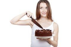 La jeune femme va couper un morceau de gâteau Photo libre de droits