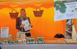 La jeune femme vend le beurre sur le marché en plein air images stock