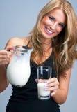 La jeune femme versent le lait dans le verre Photographie stock