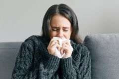 La jeune fille à la maison sur le sofa dans le chandail tricoté chaud avec un mouchoir, éternue Grippe et saison froide images libres de droits