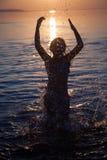 La jeune fille éclabousse l'eau au coucher du soleil Photographie stock libre de droits