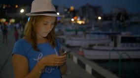 La jeune fille écrit dans le messager au téléphone portable sur le ciel nocturne de fond banque de vidéos