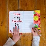 La jeune fille écrivant les mots est aujourd'hui mon jour préféré dans un journal intime de cru photos libres de droits
