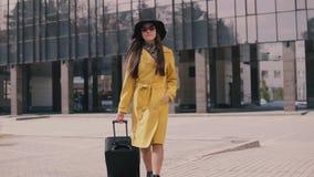 La jeune fille élégante avec une bonne humeur en chapeau jaune et verres d'imperméable vient avec le bagage clips vidéos