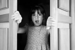 La jeune fille a étonné pour trouver et voir ce qui est derrière des portes closes Image libre de droits