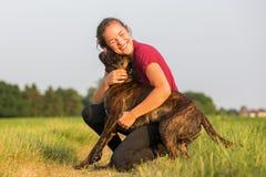 La jeune fille étreint son chien de boxeur Photographie stock libre de droits