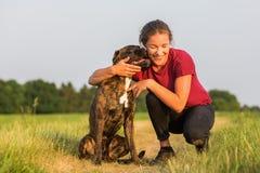 La jeune fille étreint son chien de boxeur Image stock