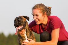 La jeune fille étreint son chien de boxeur Images libres de droits