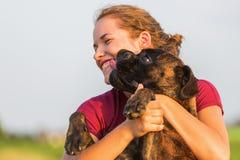 La jeune fille étreint son chien de boxeur Photo stock