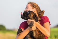 La jeune fille étreint son chien de boxeur Image libre de droits
