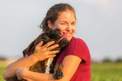 La jeune fille étreint son chien de boxeur Photo libre de droits