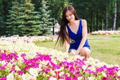 La jeune fille, étudiante, s'assied près des fleurs en parc Photographie stock libre de droits