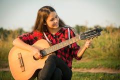 La jeune fille accorde la guitare sur le pré au coucher du soleil Photographie stock libre de droits