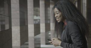 La jeune fille africaine heureuse avec du charme est riante et souriante tout en textotant, causant et passant en revue par l'int banque de vidéos