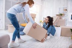 La jeune fille agréable aidant son compagnon de chambre soulèvent la boîte images stock