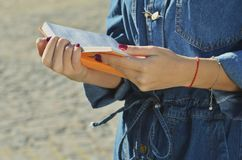 La jeune fille anonyme utilisant une veste de denim tient un livre orange ouvert dans des ses mains images stock