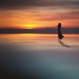 La jeune fille apprécie un beau coucher du soleil Photographie stock libre de droits