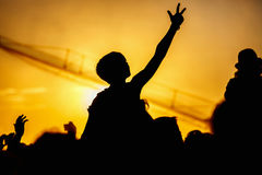 La jeune fille apprécie un concert de rock, silhouette sur le coucher du soleil Image stock