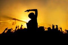 La jeune fille apprécie un concert de rock, silhouette sur le coucher du soleil Photos libres de droits