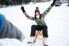 La jeune fille apprécient tandis que son ami sledding la dans beau f Photographie stock