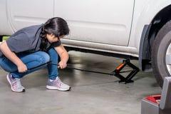 La jeune fille asiatique emploie un cric de voiture pour le soulever jusqu'au pneu de changement Photos stock