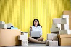 La jeune fille asiatique est début d'indépendant vers le haut de petite adresse d'écriture d'entrepreneur sur la boîte en carton  image libre de droits
