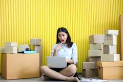 La jeune fille asiatique est début d'indépendant vers le haut de petite adresse d'écriture d'entrepreneur sur la boîte en carton  photos stock