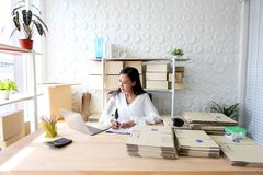 La jeune fille asiatique est début d'indépendant vers le haut de petite adresse d'écriture d'entrepreneur sur la boîte en carton  photographie stock libre de droits