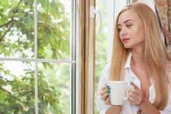 La jeune fille attirante détend avec la boisson chaude Images stock