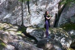 La jeune fille attirante dans les montagnes tient un tapis de yoga images stock