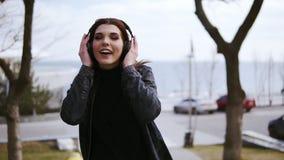 La jeune fille attirante de brune avec les écouteurs sans fil noirs dessus marche quelque part, écoute et chante en musique clips vidéos