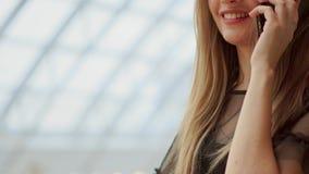 La jeune fille attirante va faire des emplettes dans le mail, parlant au téléphone, concept de achat, concept de mode, concept de banque de vidéos
