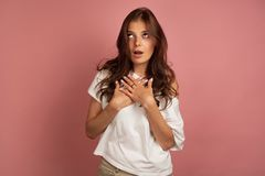 La jeune fille aux cheveux foncés dans un T-shirt blanc met ses mains à son coffre comme si elle exprime la stupéfaction, fond ro images stock