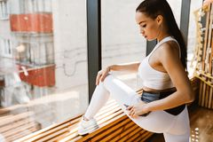 La jeune fille aux cheveux foncés mince habillée dans des vêtements blancs de sports fait l'étirage près de la fenêtre dans images stock