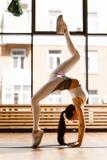 La jeune fille aux cheveux foncés mince habillée dans des vêtements blancs de sports fait l'exercice gymnastique près de la f image libre de droits