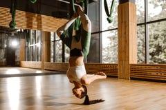La jeune fille aux cheveux foncés mince habillée dans le dessus et des collants blancs de sports fait le yoga sur l'hamac vert photographie stock