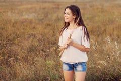La jeune fille avec de longs cheveux bruns juge un paquet d'oreilles disponible images stock