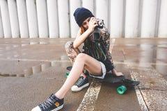 La jeune fille avec des tatouages et des dreadlocks dans un chapeau de bleu photographie un appareil-photo de vintage sur le fond photos libres de droits