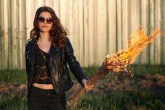 La jeune fille avec des verres et un despote noircissent la veste tenant la torche dehors Photo stock