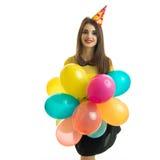 La jeune fille avec du charme avec un cône sur ses regards de sourire de tête directement et garde beaucoup de ballon à air chaud Photos stock