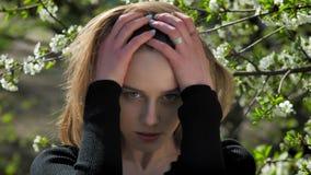 La jeune fille avec du charme pousse ses cheveux en parc pendant la journée en été, observant à l'appareil-photo, arbre de fleur  banque de vidéos