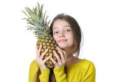 La jeune fille avec du charme presse pour faire face au grand ananas mûr Photos libres de droits