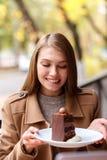 La jeune fille avec l'appétit regarde un dessert de chocolat Dans le café dehors photo libre de droits