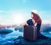 La jeune fille avec la valise s'assied sur une pierre image libre de droits