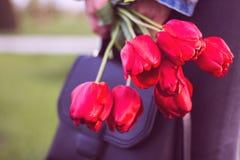 La jeune fille avec le bouquet des fleurs et du sac de tulipes marche en parc Photos stock