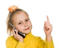 La jeune fille avec le téléphone portable affiche un doigt vers le haut Photographie stock libre de droits