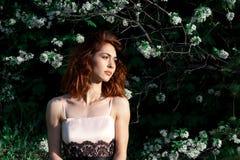 La jeune fille avec les cheveux rouge foncé magnifiques sur un fond de vert fleurit la nature Pommiers en fleur Jardin de source  photo libre de droits